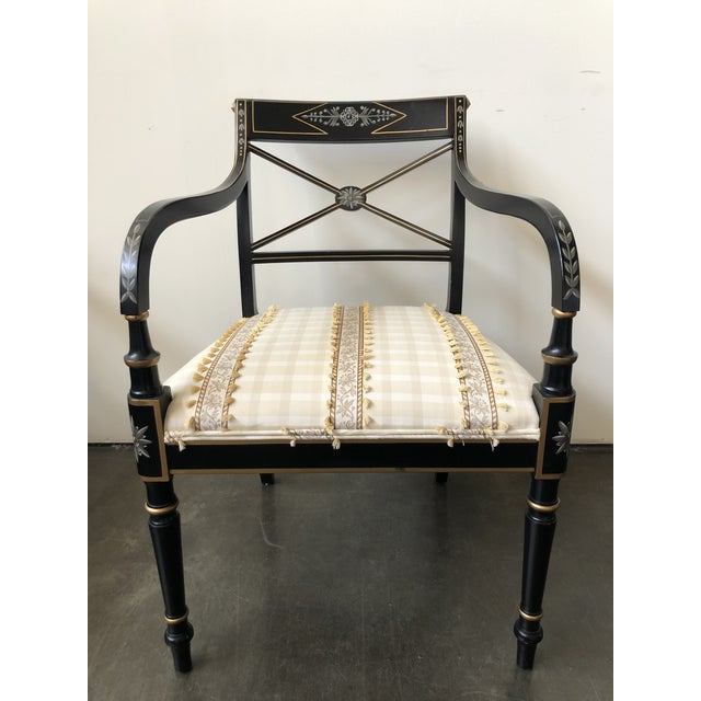Pair of Regency-style arm chairs. Frames are of solid wood painted black with painted accents in gold, white and shades of...