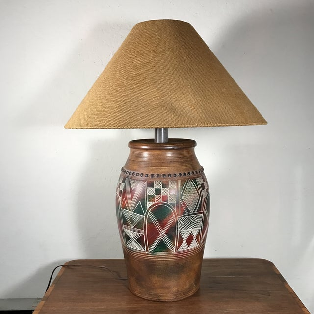 "Cool pottery lamp with tribal design and burlap lamp shade. The lamp is marked ""Casual Lamps 1993"". This lamp is in..."