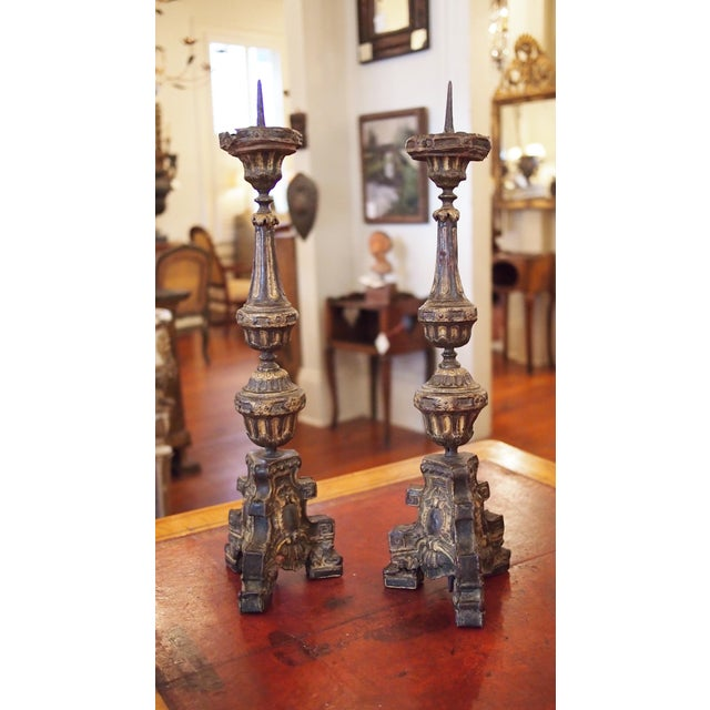 A pair of late 17th, early 18th century repousse tole candlesticks, each pedestal base on three feet and supporting an urn...