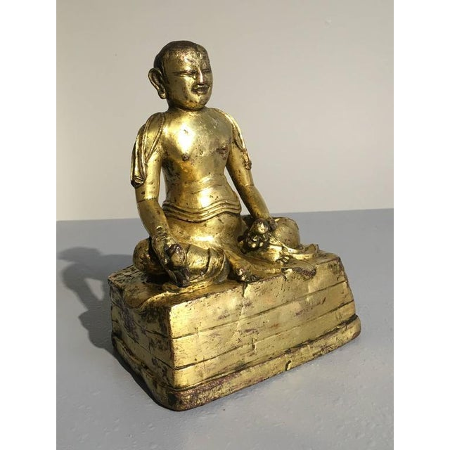 An unusual Tibetan gilt bronze figure of an arhat, one of the original disciples of the Buddha. This figure has been...