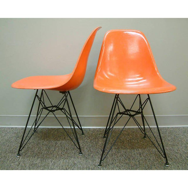 A fine pair of orange fiberglass side chairs designed by Charles and Ray Eames for Herman Miller in 1950. The chairs have...