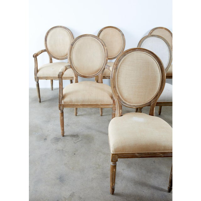 Large set of ten weathered oak dining chairs made in the neoclassical French Louis XVI taste. The set consists of five...