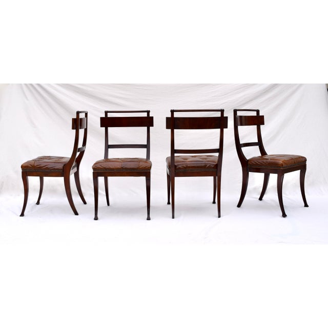 A pair of Henredon antique styled dining chairs, Federal period inspired. Channeled, flame mahogany frame of long slender...