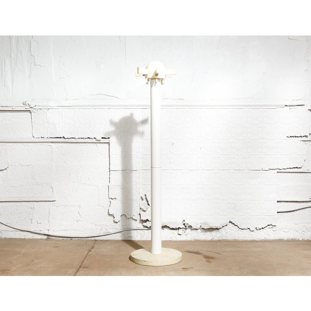 """White plastic coat rack on round base. Size: 66""""H x 18""""W x 18""""D Year: ca 1970 Status: Good condition, tip of one hook..."""