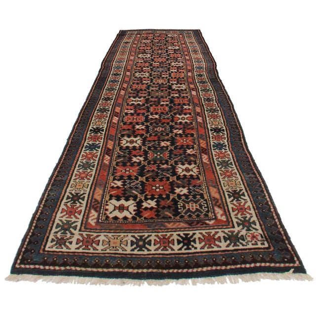 Offered is this antique Russian runner. Hand-knotted from wool. Lovely geometric design of red, blue, and cream.