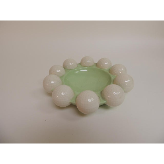 Celadon green and white glazed ceramic round golf balls ashtray from 1980's Holland. The golf balls have realistic details.