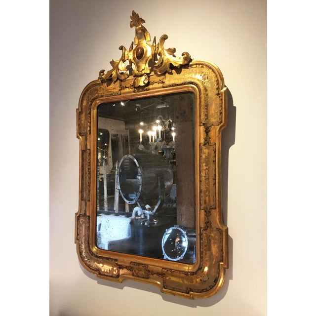 A pair of Venetian mirrors c. 1800, Italy. This pair of mirrors has new antiqued glass set in original gold Venetian...