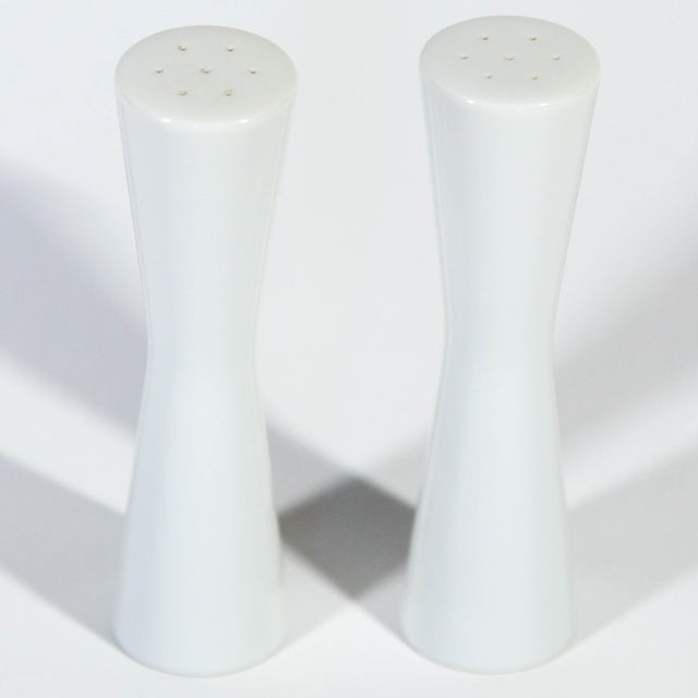 Sleek modernist white porcelain bow-form salt and pepper shakers, c. 1960s. Excellent unused condition. OMC Japan labels...