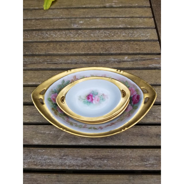 A little set of RS China from Germany nut bowl and dishes. each piece has lots of gold and two pink roses with green...