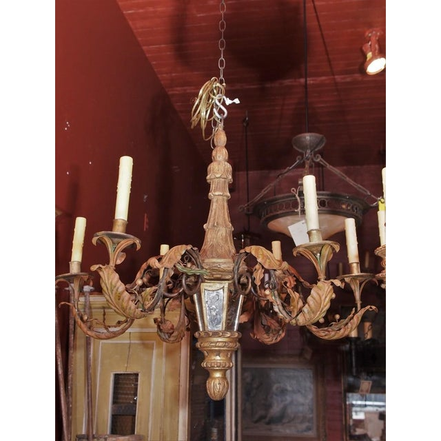 Unique French antique chandelier . Carved gilt wood shaft with 6 mirror insets. 6 lights. Iron arms are adorned with...