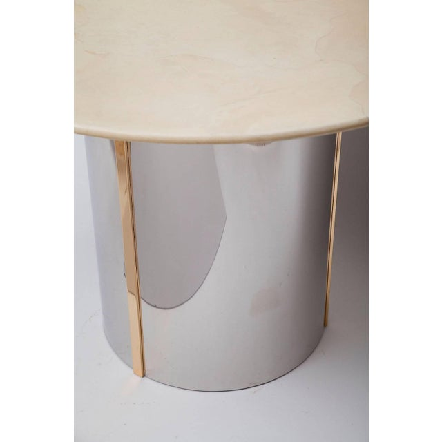 Finely-crafted center table in the style of Karl Springer has a polished steel and brass base with pale goatskin top....
