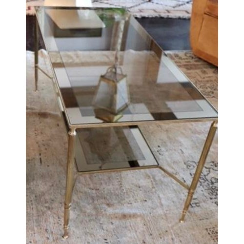 Fabulous mid-century brass coffee table, features a two-tiered smoked glass top and shelf. A very elegant design...