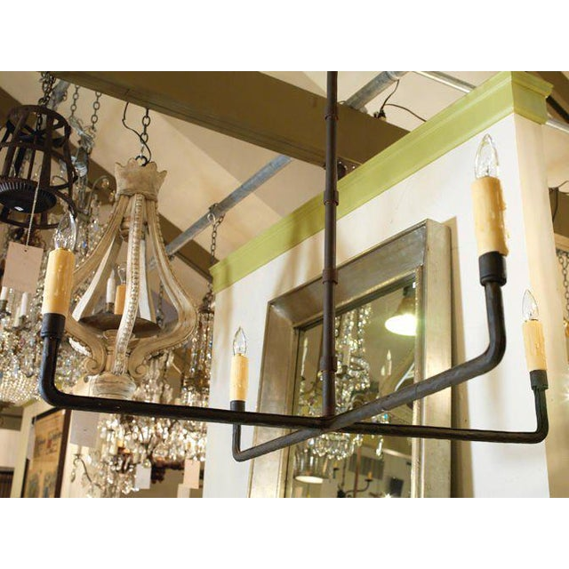 Hand-wrought, simple iron sculptural 4 light chandelier. Features four candelabra sockets, newly wired in the USA with all...