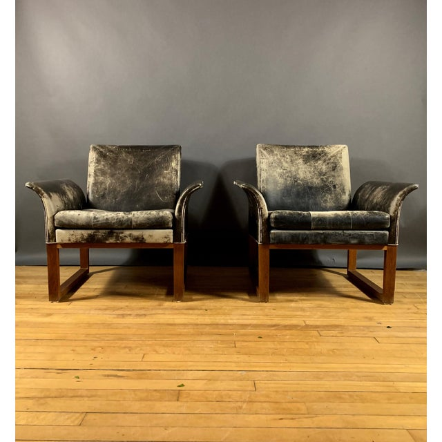 We are uncertain as to maker - though likely of Danish mid-century modern design aesthetic. The pair has sleek curved arms...