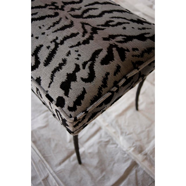 Neoclassical inspired Francois Ottoman has a hand-forged base featuring sabre legs. Upholstered in Scalamandre's Tigre in...