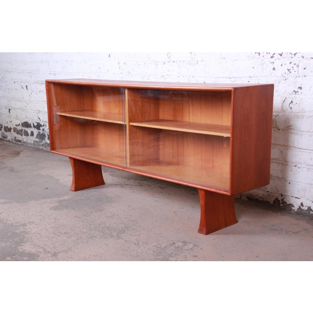 A stunning mid-century Danish Modern teak glass front bookcase or credenza. The credenza features beautiful teak wood...