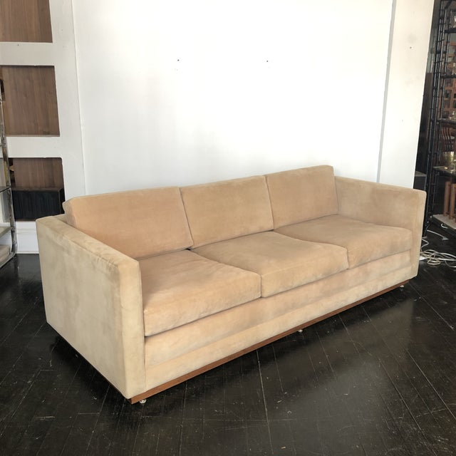 1960s Walnut Plinth Base Sofa by Mueller Widdicomb. Reupholstered in the 1990s in Cream Ultrasuede Fabric. Very clean and...