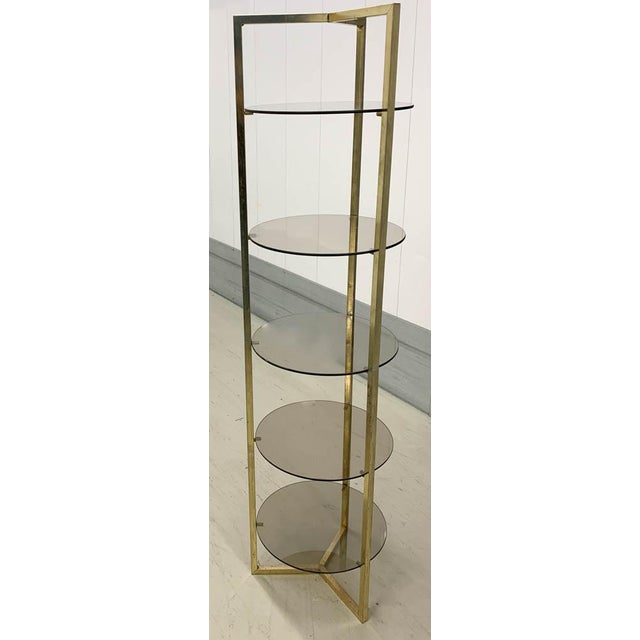 This mid century etager is in an unusual form. Vertical and sleek, the tri pod brass frame supports 5 round glass shelves....