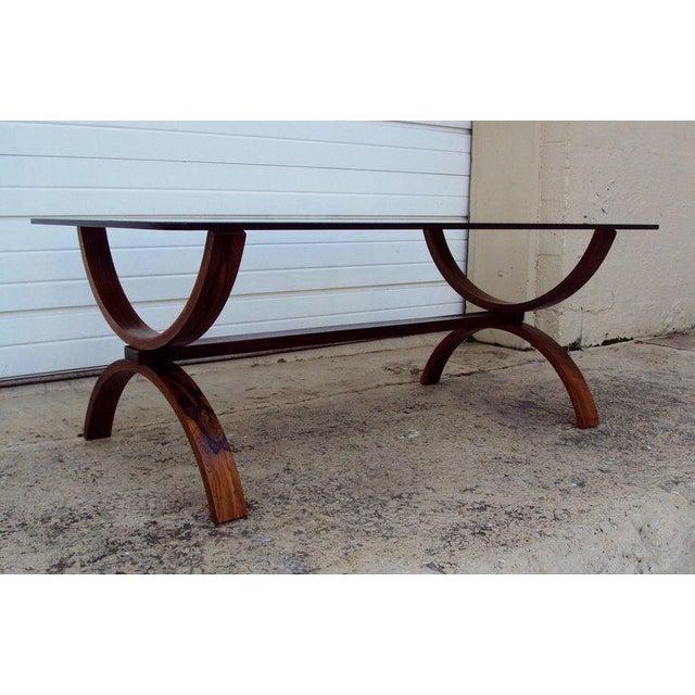 Cantilevered coffee table of jacaranda wood with original smoke glass top.