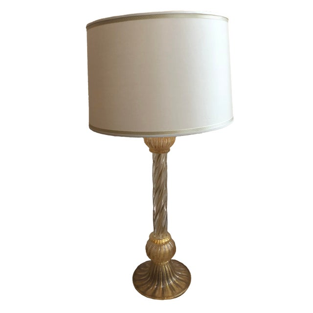 A striking pair of hand-blown Murano Glass Table lamps. Elegant curved style with flair at the base. The gold and flecked...