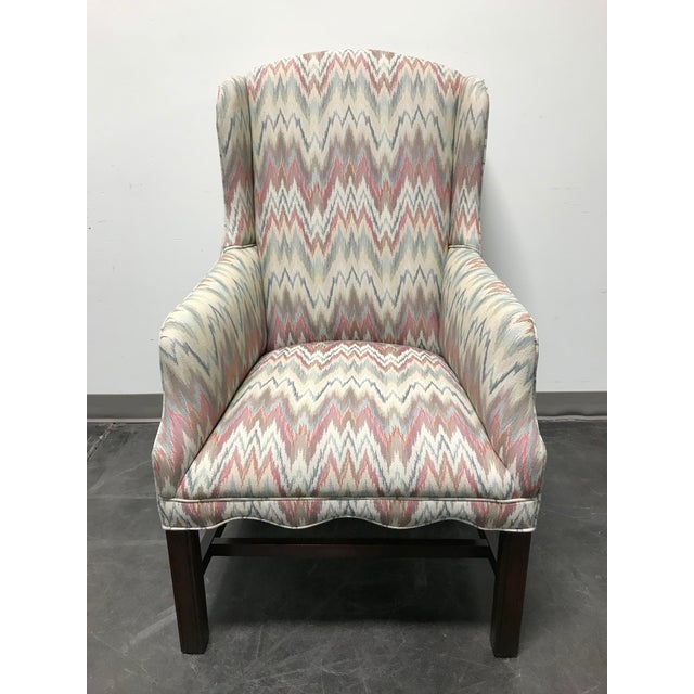 Here is a very clean wingback chair. Stretcher style mahogany wood frame, flame stitch pattern fabric. Traditional Style....