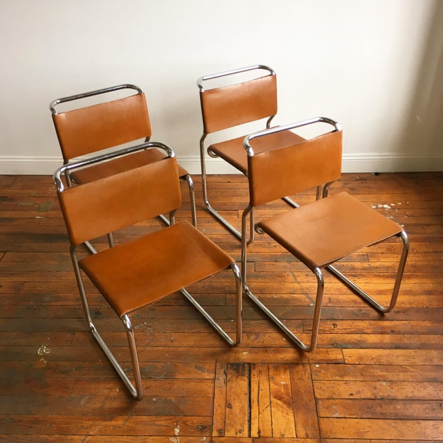 Set of four cantilever dining chairs designed by Greek American minimalist designer Nicos Zographos. The chairs are made...