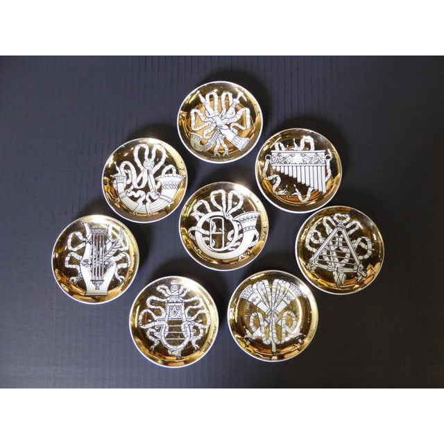 Elegant and pure Fornasetti, these eight gilt, black and white dishes featuring neoclassical visions of musical...