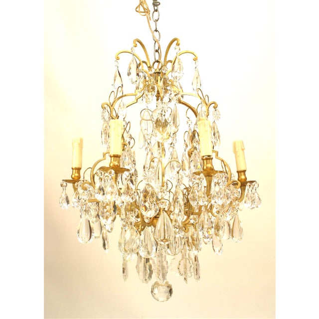 Turn of the century French Louis XV style bronze 6 light chandelier with multiple tiers of shaped crystal drops.