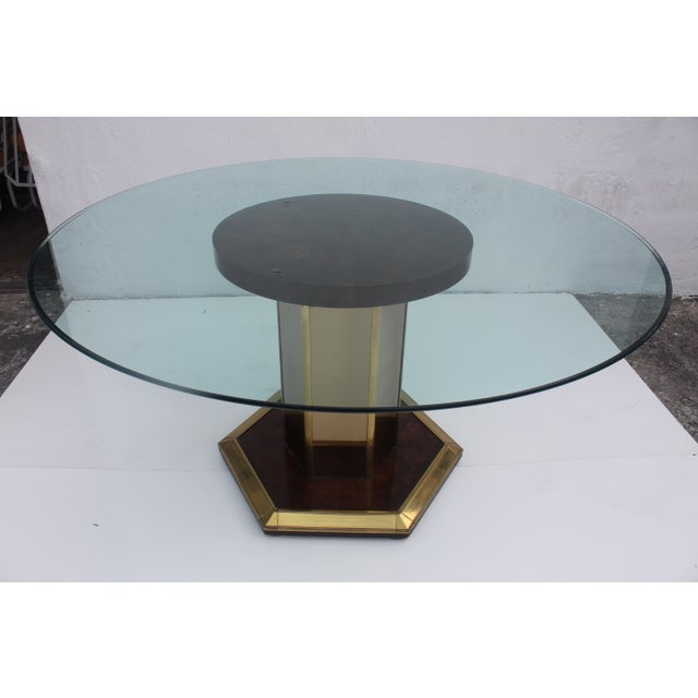 A large mid-century modern Mastercraft burled wood and brass dining table. In excellent condition. Dining table with glass...