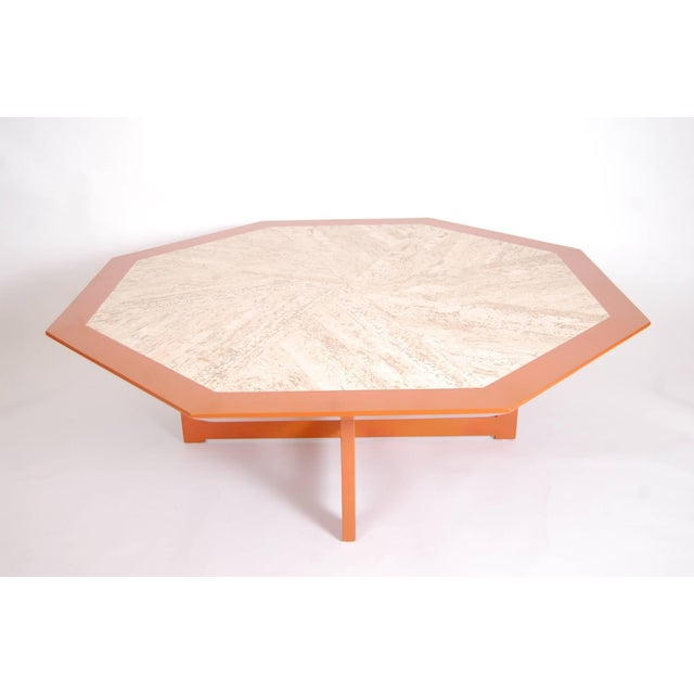 Octagonal travertine top coffee table in orange lacquer, designed and produced by Harvey Probber, circa 1958.