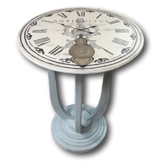 A sweet little accent table with a hand painted design of a French clock. The gorgeous curved legs and base are painted...