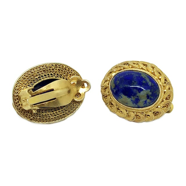 Circa 1950s to 1960s Chinese gold-plated sterling silver clip-back earrings set with oval sodalite cabochons. They are...