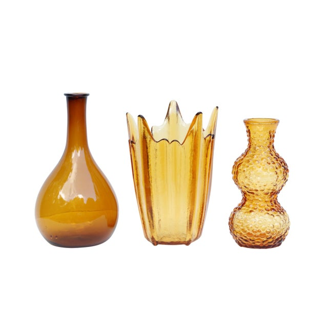 A set of three striking amber glass vases. The tallest is a clear blown glass flask with a slender neck and rounded base,...