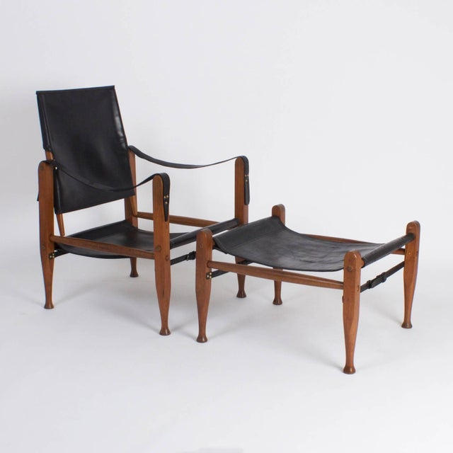 Dapper, Mid-Century safari chair and ottoman crafted with mahogany and soft black leather. Featuring swivel back, sling...