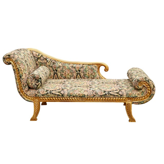 A Hollywood Regency chaise longue. Upholstered in a rich floral jacquard in pastel tones over a black base. The giltwood...