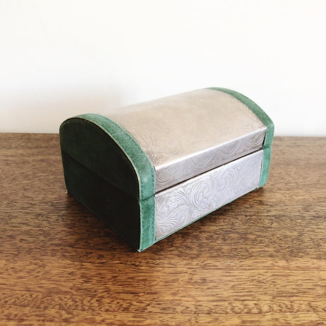 Vintage embossed tin box with green velvet lining and trim and a mirror inside the lid.