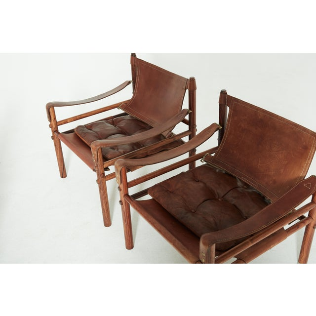 A very rare set of four authentic vintage Arne Norell safari sirocco chairs in rosewood and beautifully patinated brown...