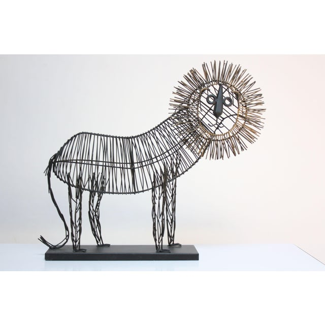 Contemporary (late 20th Century) lion sculpture composed of painted, bent metal wire rods. (Aside from the gold mane, the...