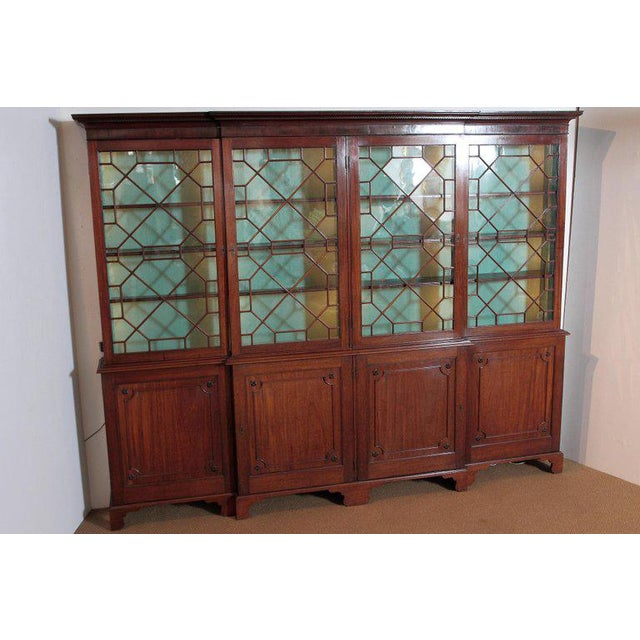 A large Georgian mahogany breakfront bookcase with carved Greek Key trimmed cornice above four mullioned glass doors. The...
