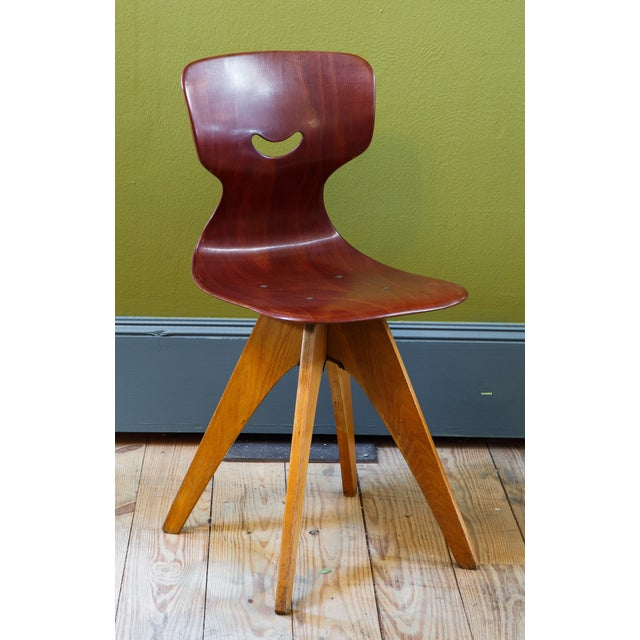 Set of four plywood curved chairs in the Mid Century Modern style. Unusual wooden splayed legs and cut out back. These...