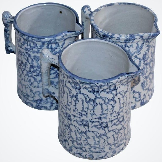 This is a collection of three spongeware water pitchers. The shapes are slightly different and all in good condition.