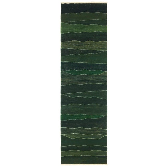Created using finely hand-spun wool and vegetal-dyes, this richly hued tone-on-tone green runner features traditional...