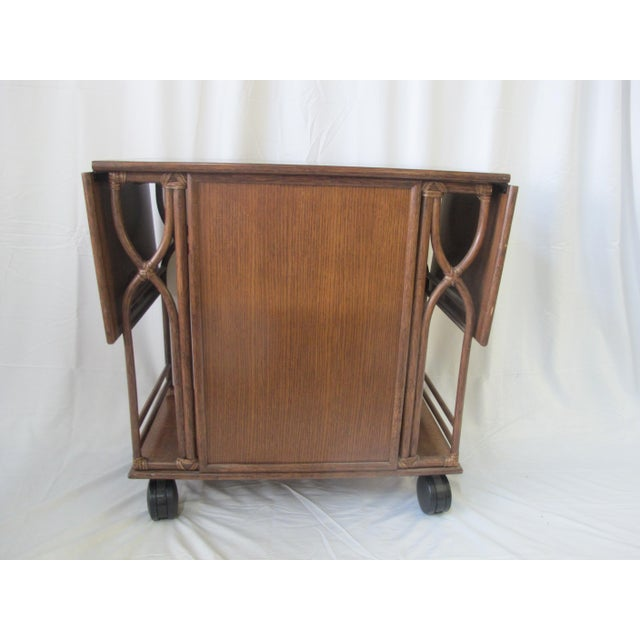 McGuire mid-century dry bar rolling cart with two drop leaf sides. Front door opens up with gold tiki style handle to 3...