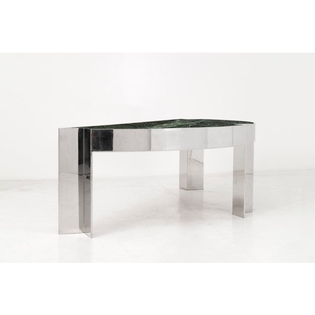 Arced desk with a polished steel frame and verde marble top. Two drawers with laminate fronts and wood inner. Armchair...