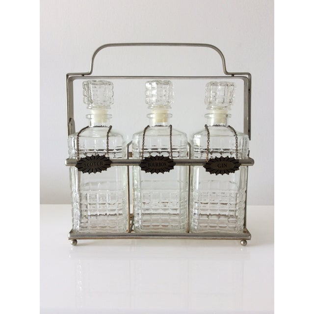 Three cut glass decanters set with metal carrier/tantalus which can be locked for safety. Three metal decanter labels...