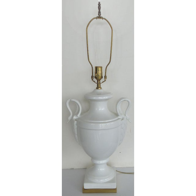 A classical white ceramic table lamp from Paul Hanson with swan handles and supported by a brass base. The knob on the...
