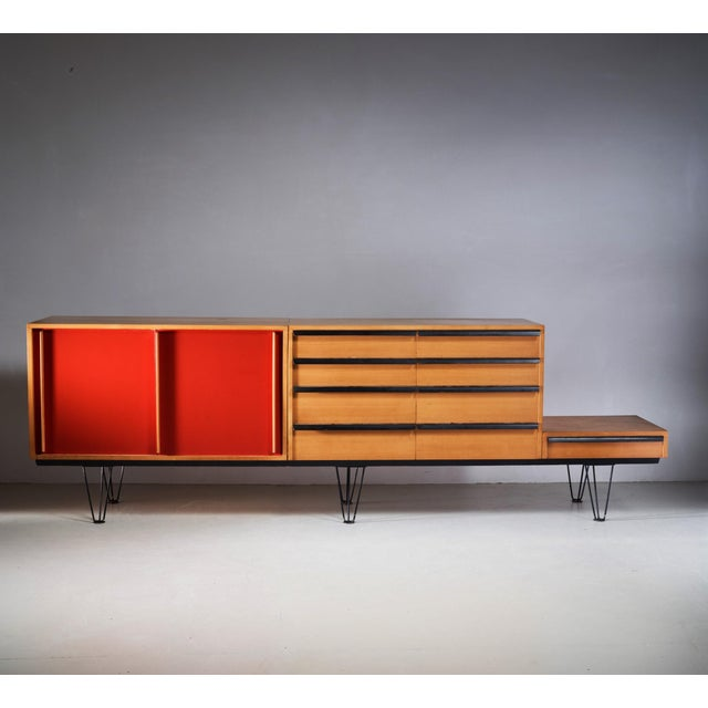 A sideboard by Swiss designer Alfred Altherr. This modular piece has three beech storage units; one with two red sliding...