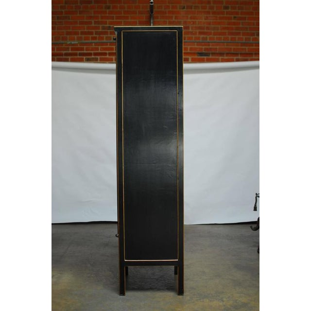 Sleek Chinese tall black lacquer cabinet made in the Ming style fronted by two narrow doors, made with wood hinges....