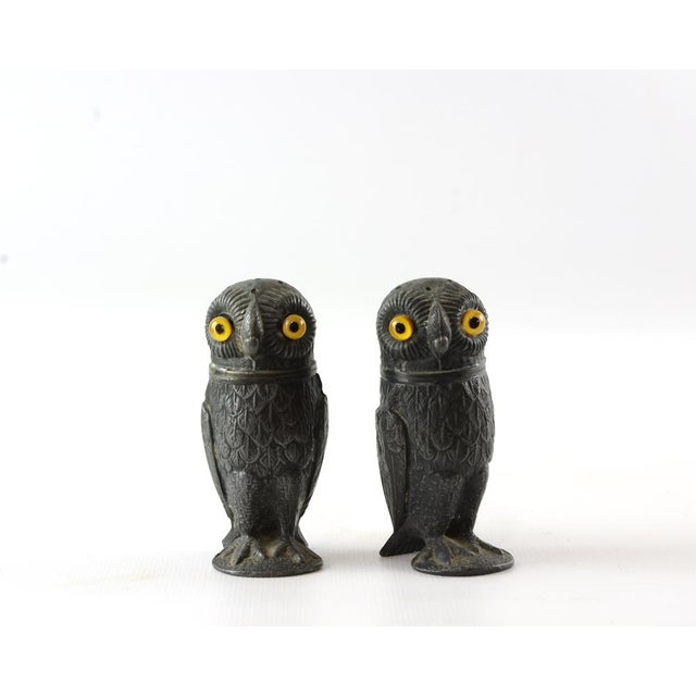 These wonderful antique pewter owl pepper pots have nicely detailed feathers and amber glass eyes. The heads of the salt...