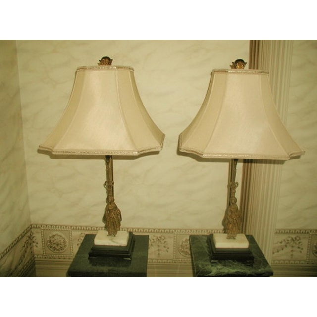 Handsome pair of French early 1900's Girandole lamps. Mounted on black wood bases, the off white marble shows hints of...